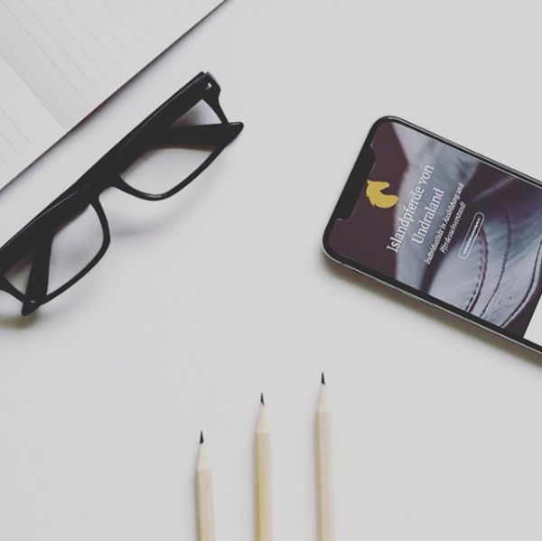 Brille, 3 Bleistifte und ein Handy auf einem Tisch
